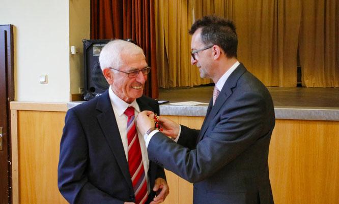 Umweltminister Reinhold Jost steckte Günter Lang das Kreuz an.