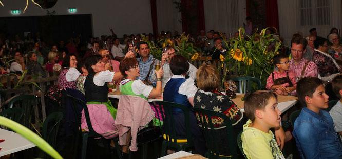 Die Gäste im Ruppertshofsaal heben ihre Gläser zu Ehren der neuen Erntekönigin.
