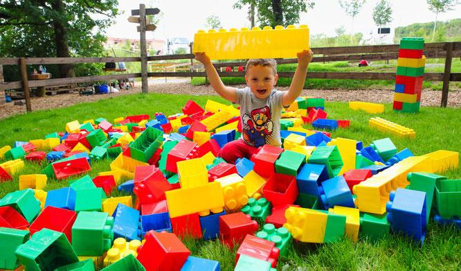 Auf der Spielwiese liegen viel große und bunte Bausteine für die Kinder bereit.