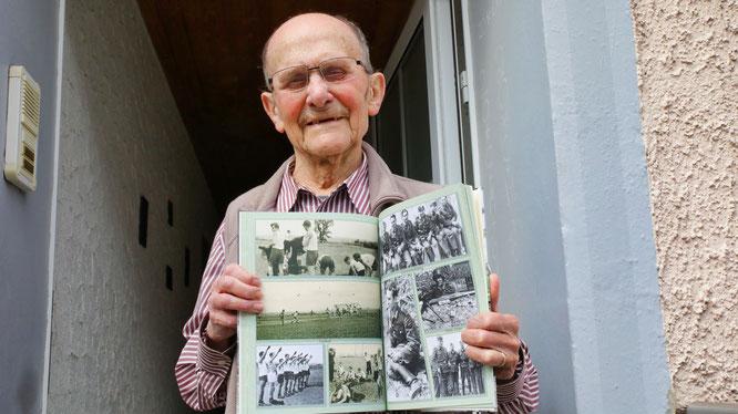Albert Wolf mit einem Fotobuch mit Fotos aus dem Zweiten Weltkrieg, die er selber geknipst hat.