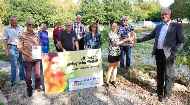 Jurymitglied Hans Scholten (rechts) überreichte Rebekka Nadig und allen anderen Mitgliedern des Vereins für Dorfentwicklung Kleinblittersdorf die Auszeichnung der UN-Dekade.