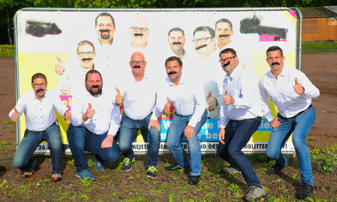 Die FDP in Kleinblittersdorf hat sich aus einem Ärgernis einen Spaß gemacht und mit aufgeklebten Schnurrbärten vor einem verschmierten Plakat posiert.