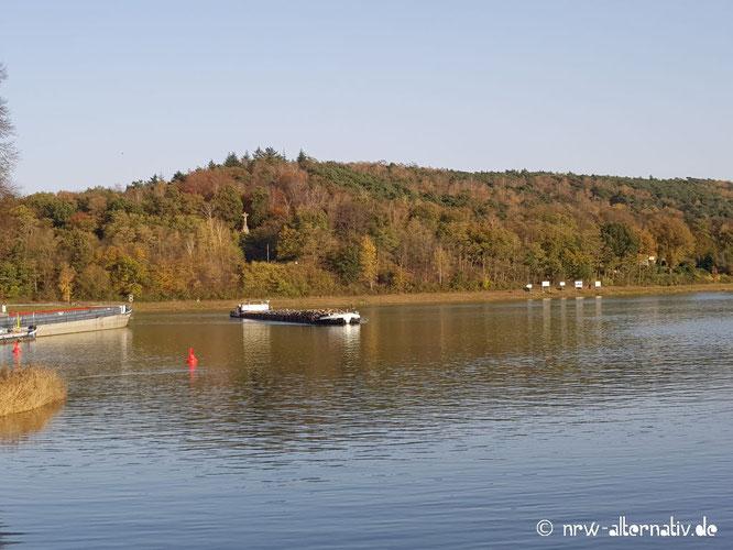 Vor einem bewaldeten Hügelkamm fährt ein Schiff auf einem Kanal.