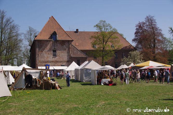 Vor einem historischen Gebäude sind historische Zelte aufgebaut, vor denen Menschen stehen.
