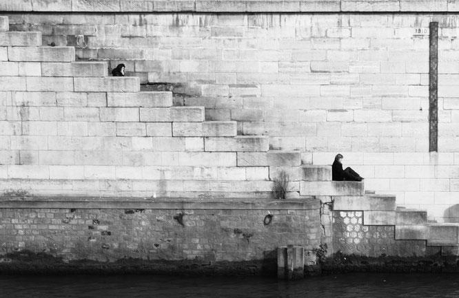 Frauen, die auf einer Treppe sitzen und in großem Abstand etwas lesen.