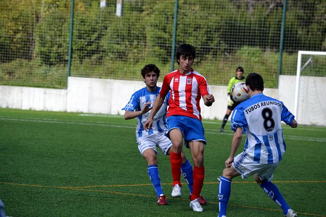 Joseba Pérez ante dos futbolistas blanquiazules en el duelo entre el Laudio B y el Amurrio de la temporada 2012-13.