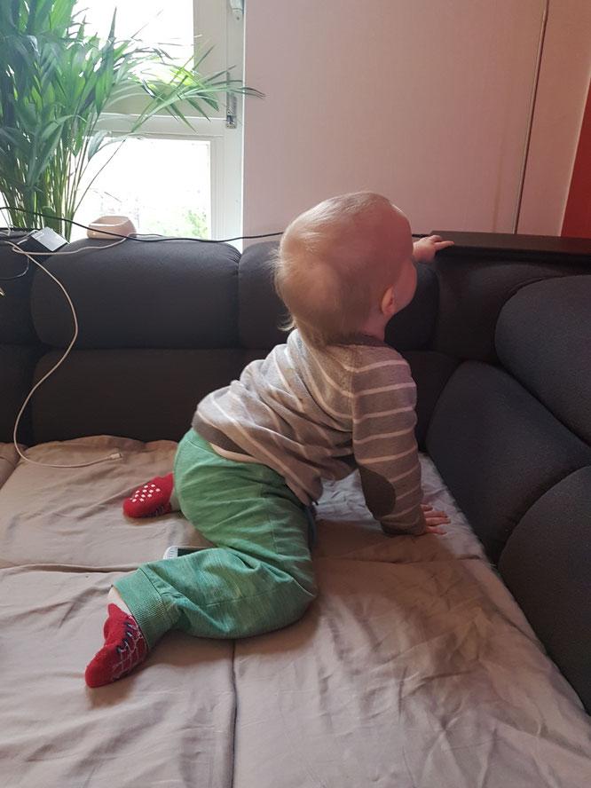 Kleinkind, 15 Monate alt, spielt gern mit Laptop, Telefon und Kabeln.