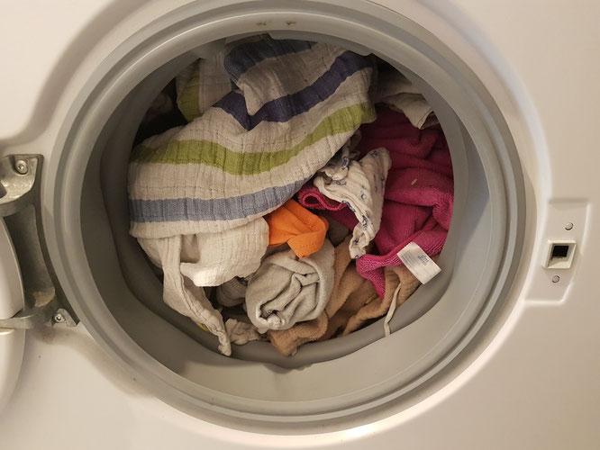 Mit Mullwindeln und Wäsche gefüllte Waschtrommel als Symbolbild für Windelfrei-Erfahrungsbericht.