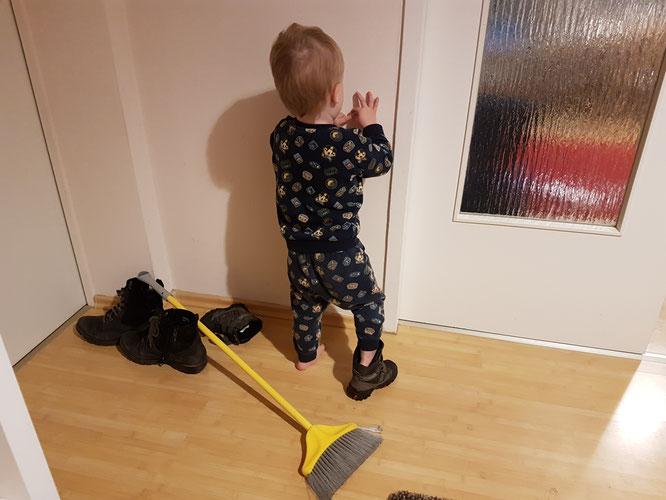 Zweijähriges Kleinkind mit angezogenem Winterstiefel und ungünstig platziertem Besen in Wohnung.