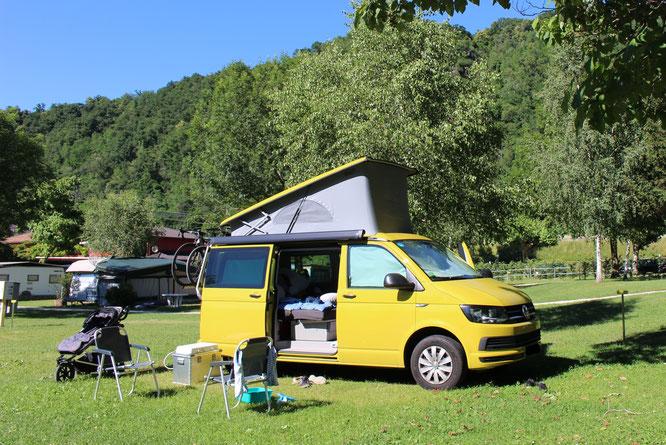 Campingplatz mit Wohnmobil bzw. VW-Bus. Ein Kinderwagen im Hintergrund zeigt, dass es ums Reisen mit Baby geht. Mama-Blog patschehand.de
