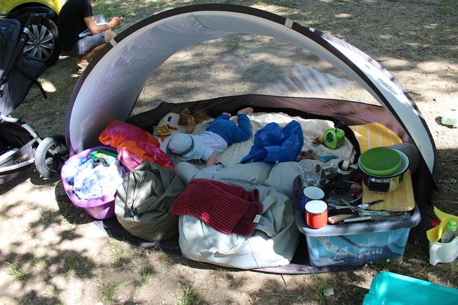 Baby in Strandmuschel auf Campingplatz.
