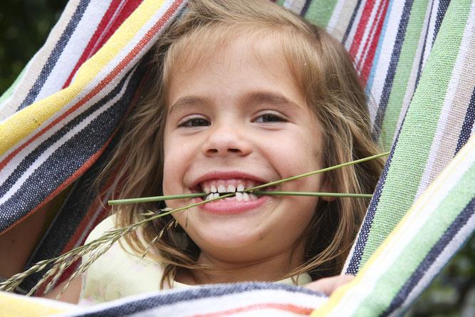 Lachendes Mädchen in Hängematte hält Grashalme zwischen ihren Zähnen.