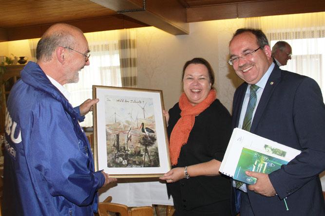 """Alfred Glener überreicht als Vorstand des NABU Euskirchen Frau Heinen-Esser das NABU-Plakat """"Wald der Zukunft"""", um auf die kritische Situation der Windkraft im Wald aufmerksam zu machen. (Quelle: EIFELON)"""