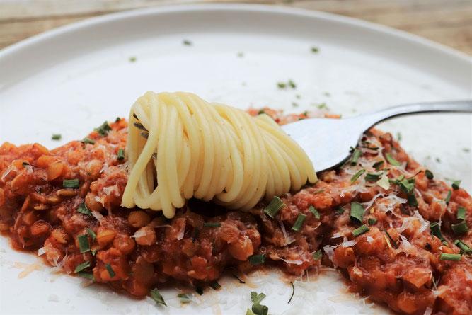 vegetarisches Linsensugo mit einer Gabel voll Nudeln