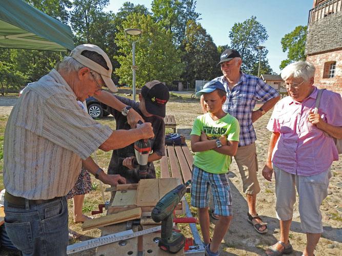 Unter Anleitung durch NABU- Mitglieder werden Fledermauskästen gebaut