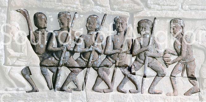 Cinq personnages dansent avec des bâtons ou des dames, accompagnés par un joueur de crotales lors de la construction d'un temple. Bayon. Galerie extérieure ouest.