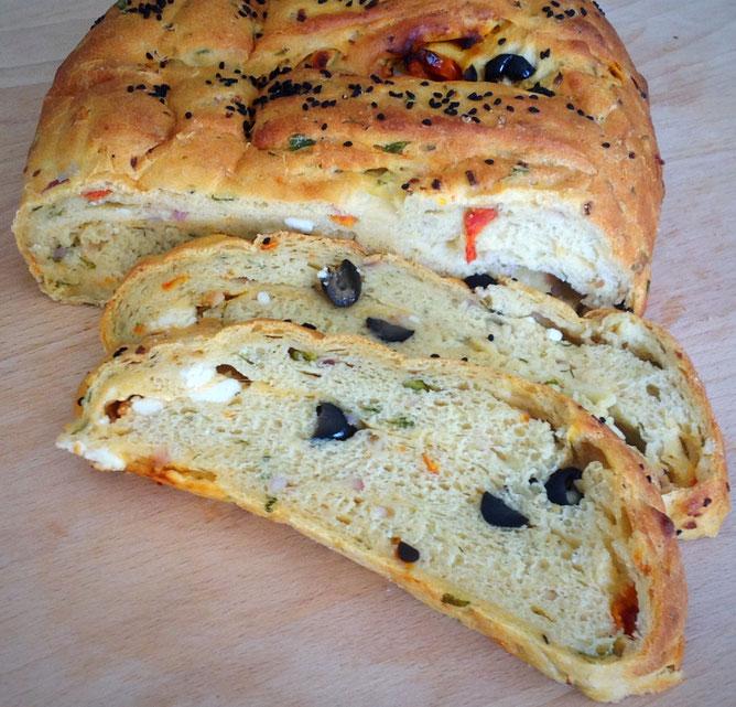 Mediterraan aardappelbrood met feta, ui, zongedroogde tomaatjes en olijven.
