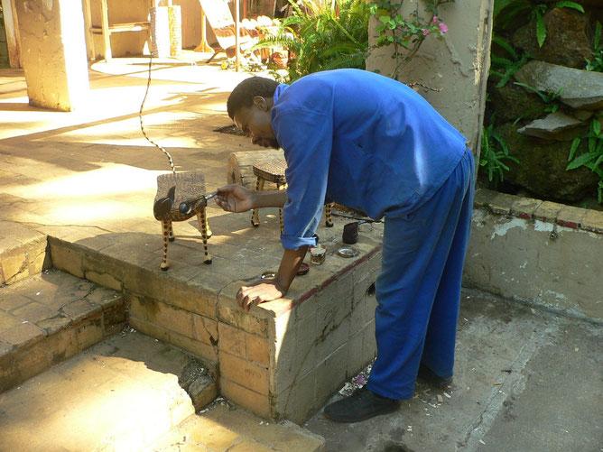Acan Masucu hat die Katze aus Jacarada Holz fertiggestellt und malt die Schnauze noch rot