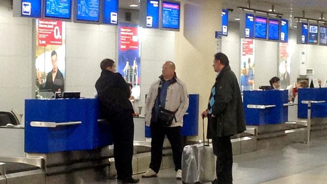 Сотрудник аэропорта Внуково, Никита и Ференс мило беседуют в зоне регистрации на международные рейсы
