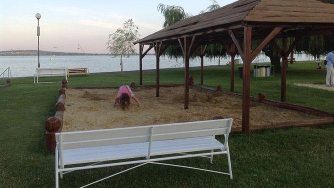 Девочка в удобной позе играет в огромной песочнице. И скамейка для родителей есть. Все продумано для полноценного отдыха и детей и взрослых.