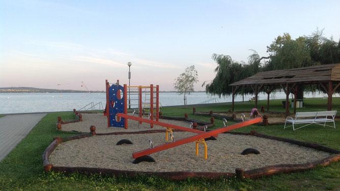 Справа от зоны кафе находится большая детская площадка. Чистый песок, качели и стенка для маленьких туристов и жителей.