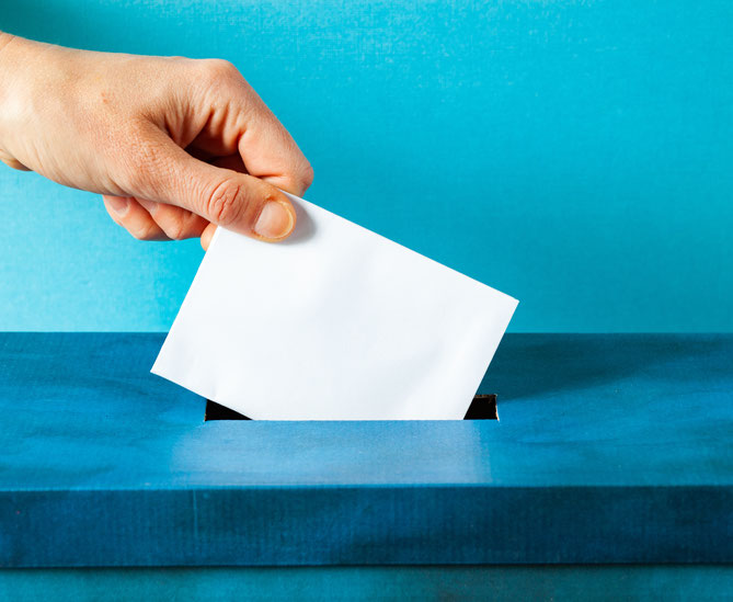 Hand putting ballot paper into ballot box