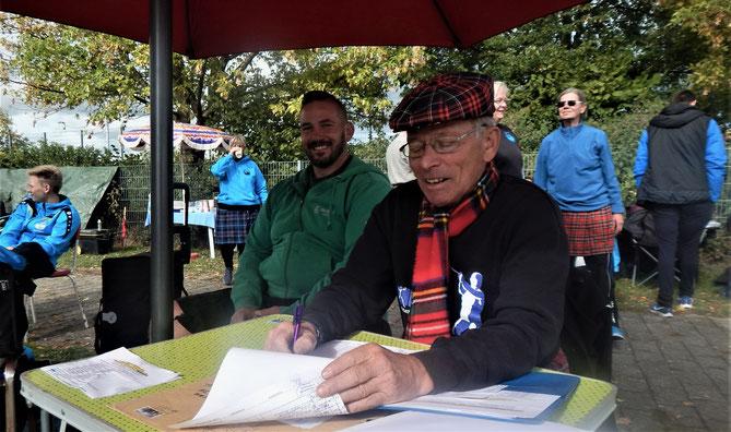 """Oberkampfrichter Jochen Heinzel in Aktion, beobachtet von """"Ober-Highlander"""" Holger Karch, der wie immer Farbe in die Veranstaltung brachte."""