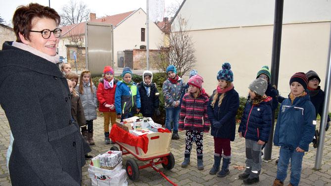 Simone Track (links), Pflegedienstleiterin des Pfaustifts überreicht das Dankeschön an die Kinder.