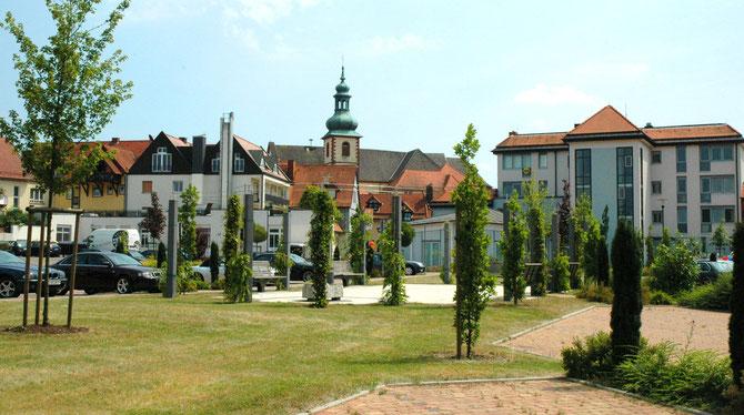 Hinter dem Rathaus in Flieden mit Sicht auf die Kirche St. Goar und den Bäcker Happ - WIFO Flieden