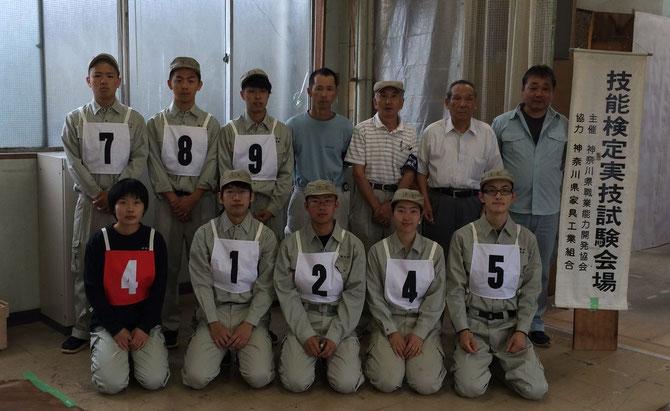 2015年7月5日、技能検定家具手加工1級(赤)と技能五輪(白)の受験者と検定委員。