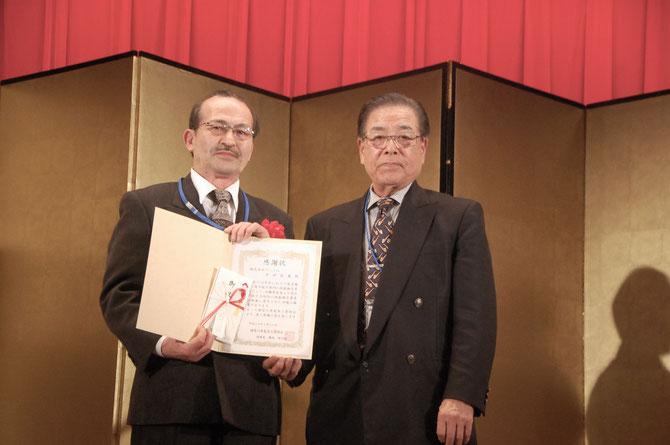 いす張り部門の技能検定委員、吉田昌義氏を横内理事長が表彰。