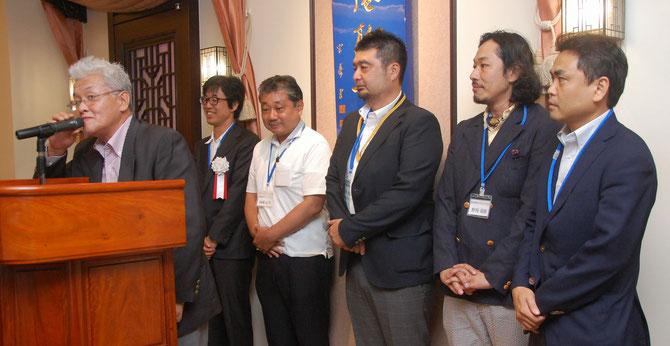かなもく塾を代表して細貝昭一氏から活動報告。後方壇上のメンバーは、左から熊谷氏、岡崎氏、横内氏、野﨑氏、咲寿氏。