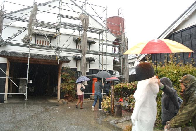 傘をさして工場見学をするフィギュア