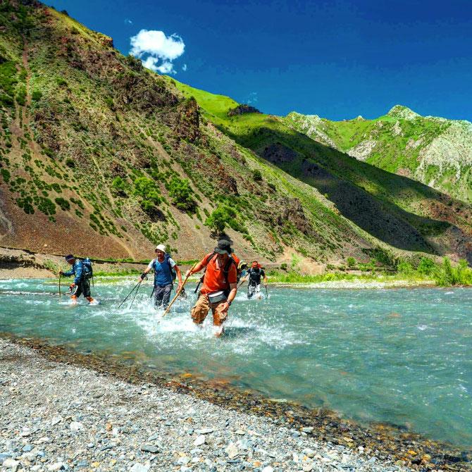 trekking in Kyrgyzstan. Crossing mountain river