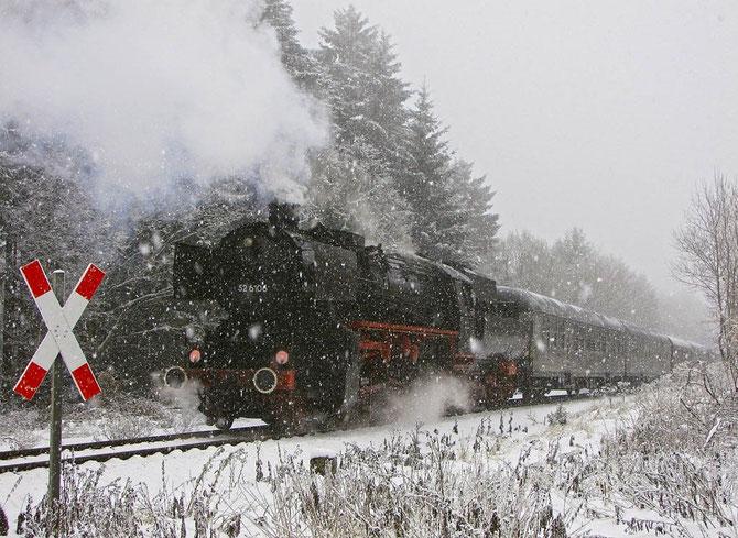 Bei heftigem Schneetreiben rollt der erste Zug des Tages bei Laubach-Müllenbach hinab nach Kaisersesch - Foto: Georg Lochner