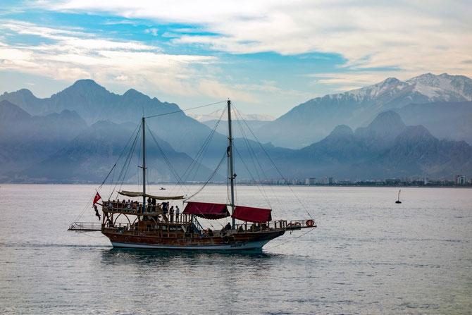 Touristenboot in Antalya vor der beeindruckenden Kulisse des Beydaĝları-Gebirges