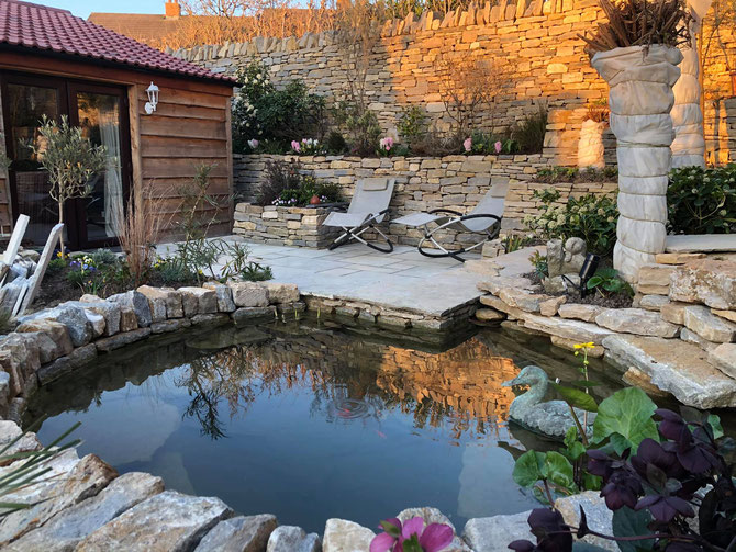 The stone creating space, and privacy, with pond as the central feature