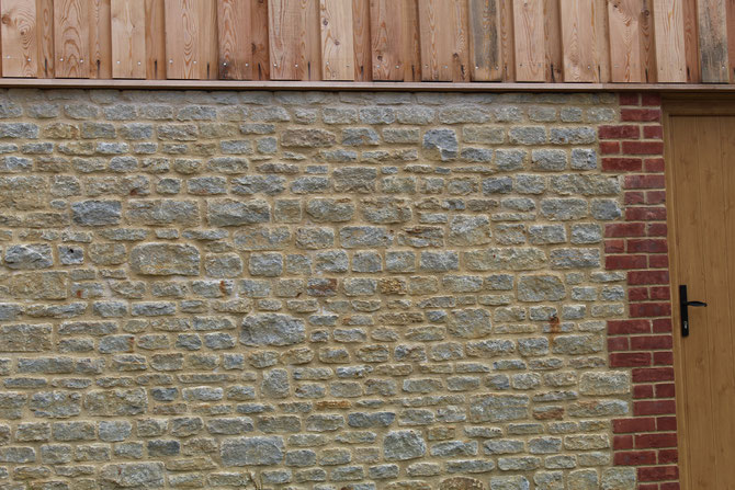 Neatly coursed building stone with brick and timber