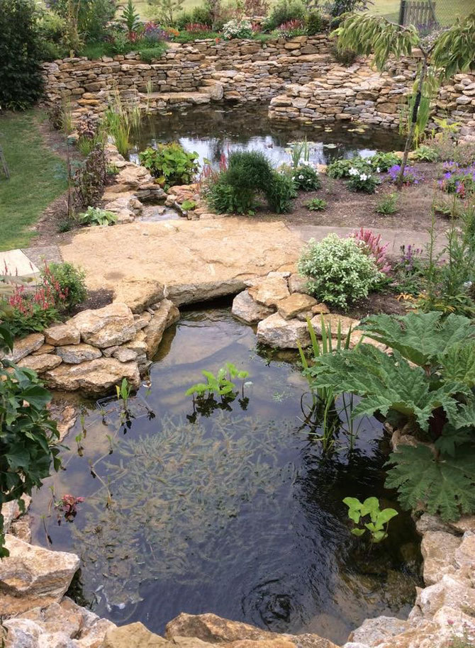 Garden pond with drystone and rockery - note the stone bridge - single piece