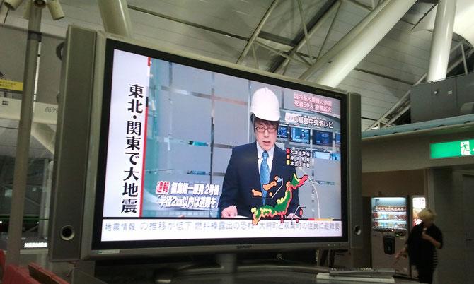 Información del gobierno en todas las televisiones (aeropuerto internacional de Kansai).  Las zonas rojas de la costa eran las alertas por tsunami de distintas alturas. El aeropuerto está justo donde termina la línea roja que va de noreste a sudeste.