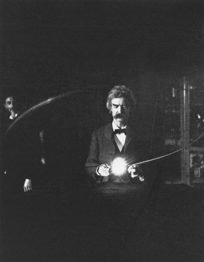 Fig. 13. — Similar experiment, the high-tension current being passed through the body before it brings the lamps to incandescence. The loop is held over the resonating coil by Mr. Clemens (Mark Twain). (From flash-light photograph.)