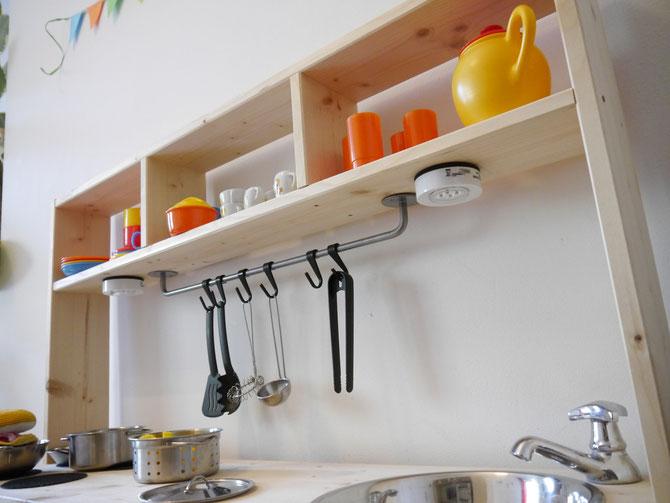 Wenn eine Küchenstange angebracht werden soll, am besten so weit wie möglich nach hinten setzen. So ist sie nicht so im Weg und die Bestecke wackeln nicht so widerspenstig, wenn die Kleinen sie abnehmen/ anhängen wollen.