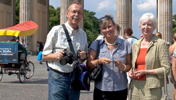 3 Personen vor dem Brandeburger Tor lächeln zur Kamera. Man sieht nur die Säulen, das Bild reicht bis zum Gürtel der Personen. Links mit Kamera ist Peter Bach, in der Mitte mit Handy Renate Bach, rechts ist Petra-Ines Kaune.