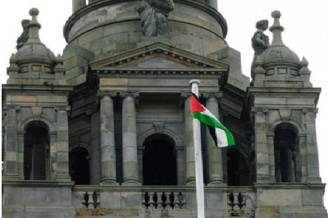 14 AOÛT 2014. SADIE DOCHERTY HISSE LE DRAPEAU PALESTINIEN DEVANT SA MAIRIE EN SOUTIEN à GAZA CONTRE LES MASSACRES  PERPETRES PAR  L'ARMEE ISRAËLIENNE.