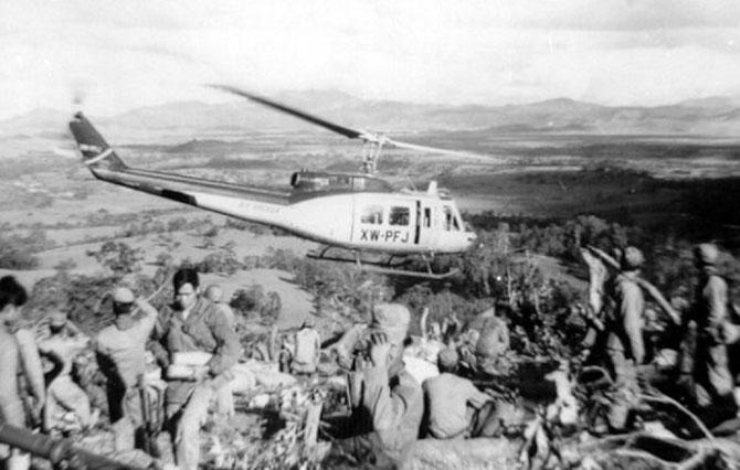 1969. AIR AMERICA BELL 205 ( version civile de l'armée UH-1 HUEY) quittant une base de pompiers Hmong au sommet d'une colline au S.E du PDJ, après avoir déposé hommes et approvisionnements.