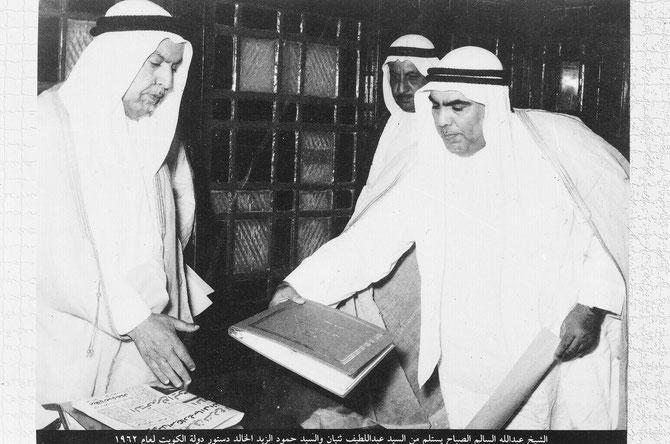 SON ALTESSE L'EMIR ABDULLAH III RECOIT LE PROJET DE LA CONSTITUTION DU KOWEÏT      (COMPORTANT 183 ARTICLES) DE LA PART DU REDACTEUR.    LA CONSTITUTION FUT APPROUVEE ET PROMULGUEE LE 11 NOVEMBRE 1962.