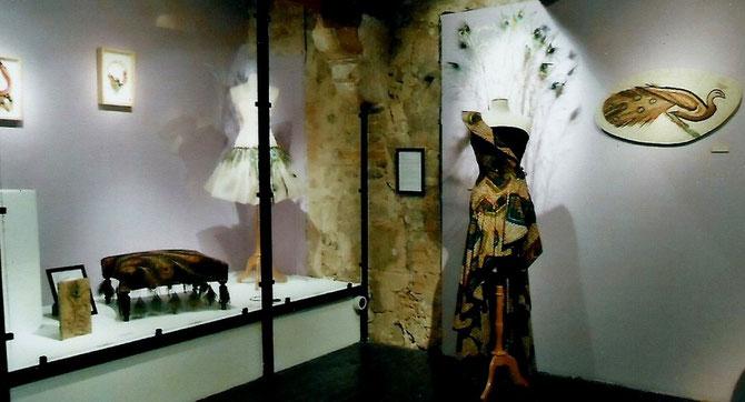 """A gauche. SYLVIE KAMENI : """"LA PARADE"""", robe en tissiu africain et plumes de paon. A droite, au mur : VANINA MERCURY : """"PAON"""" D'après une mosaîque du MUSEE DU BARDO-TUNIS"""