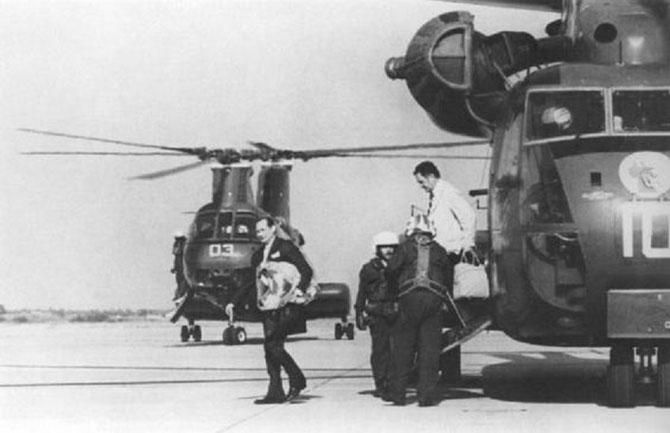 12 AVRIL 1975. PHILIPPINES UTAPAO AIR FORCE BASE. L'AMBASSADEUR DES ETATS-UNIS JOHN GÜNTHER DEAN  et LE DRAPEAU  AMERICAIN SOUS LE BRAS. C* SAL VEDER / AF