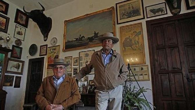 DON EDUARDO III et DON ANTONIO II DANS LE SALON DE LA MAISON REMPLIE DE SOUVENIRS.