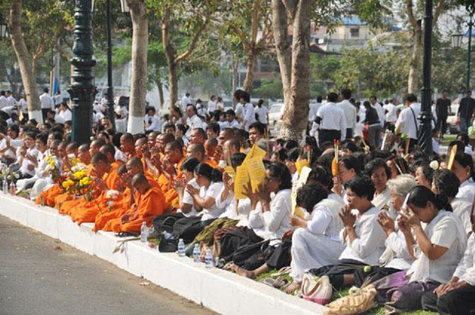 Un peuple éploré, recueilli, attend le passage de la procession à travers la ville.